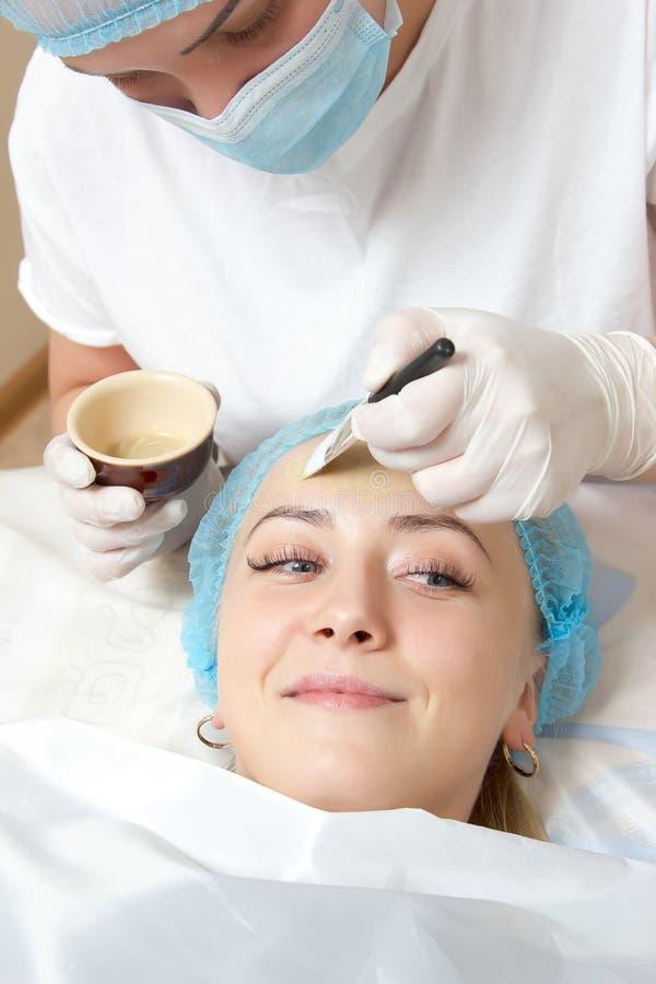 Beautician που εφαρμόζεται με ένα πακέτο προσώπου βουρτσών στοκ εικόνες