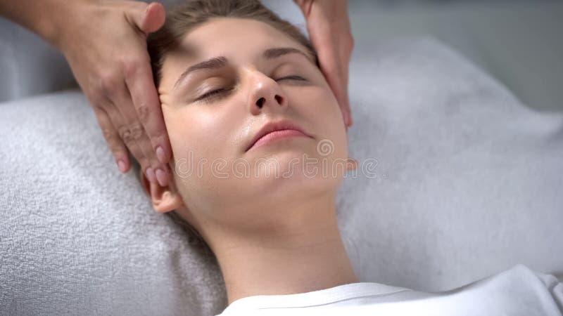 Beautician που κάνει το χαλαρώνοντας του προσώπου μασάζ, που τρίβει το rejuvenating ορό στη γυναίκα στοκ φωτογραφίες
