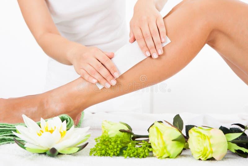 Beautician το κηρώνοντας πόδι μιας γυναίκας στοκ φωτογραφία