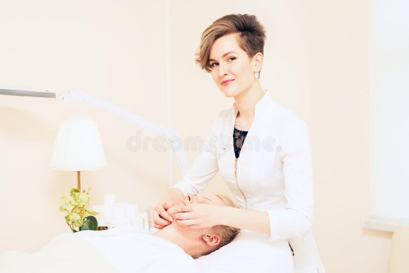 Beautician делает лицевой массаж шкаф косметологии o r стоковое фото