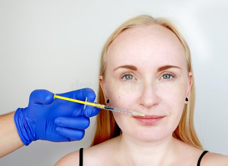 Beautician доктора проводит губы контура пластиковые: впрыска в губы, увеличение губы Hyaluronic кисловочная впрыска стоковая фотография
