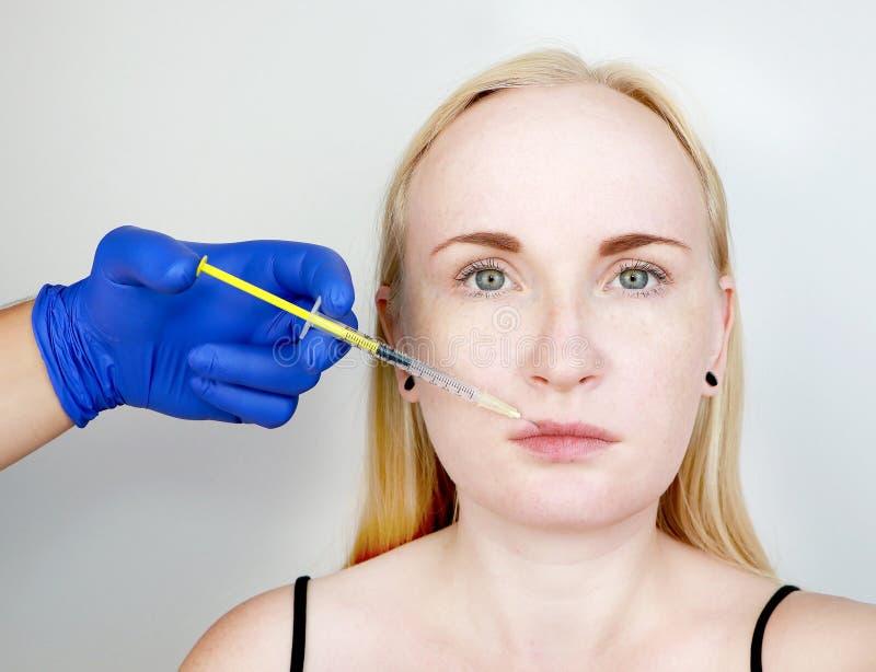 Beautician доктора проводит губы контура пластиковые: впрыска в губы, увеличение губы Hyaluronic кисловочная впрыска стоковое изображение