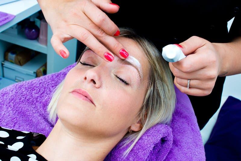 Beautician кладя сливк кожи на сторону женщины стоковая фотография rf