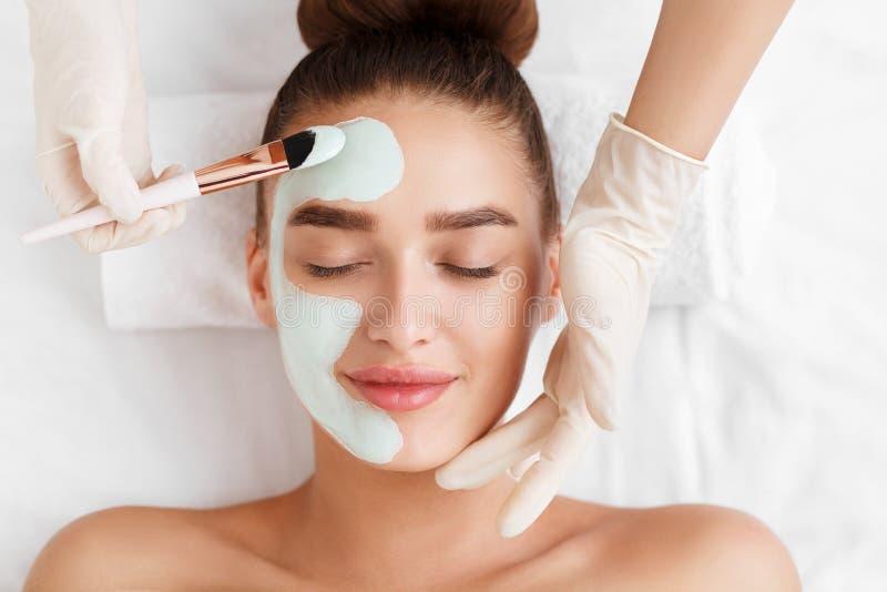 Beautician прикладывая лицевой щиток гермошлема глины на стороне женщины стоковая фотография rf