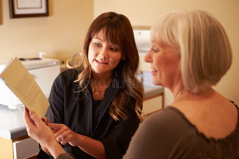 Beautician советуя женскому клиенту на продуктах красоты стоковые фото