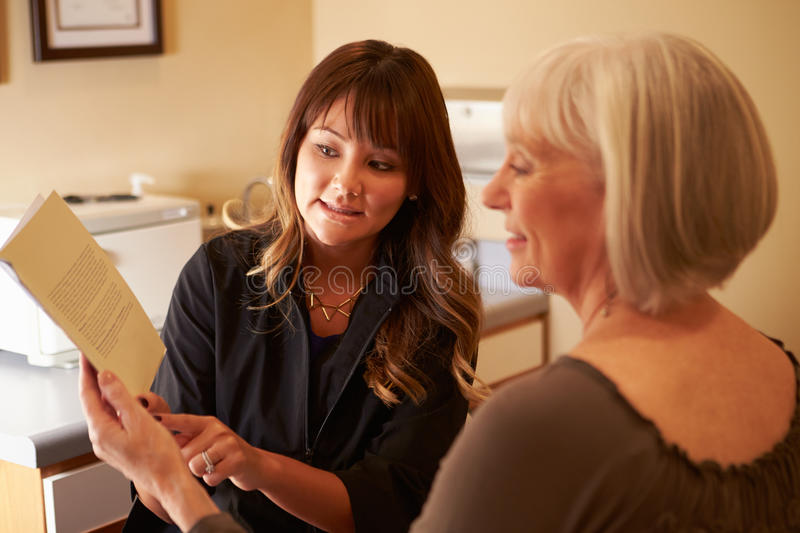 Beautician Advising Female Client On Beauty Products. Pointing At Leaflet stock photos