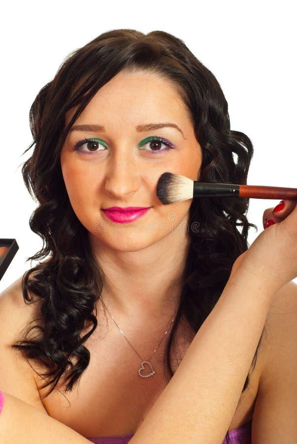 Beautician applying blush on woman face
