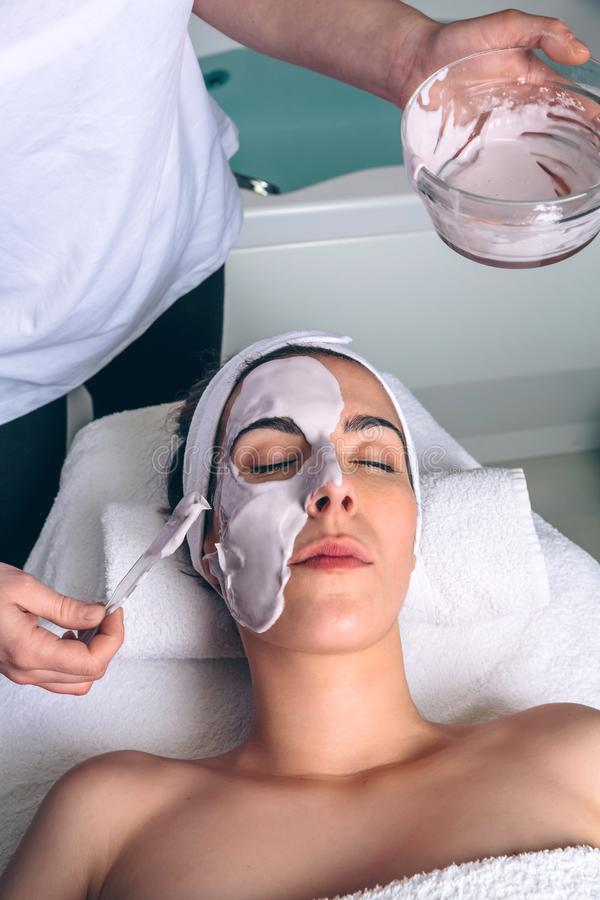 Beautician applying facial mask to woman in spa. Female beautician applying clay facial mask to young women lying with closed eyes in spa. Medicine, healthcare stock image