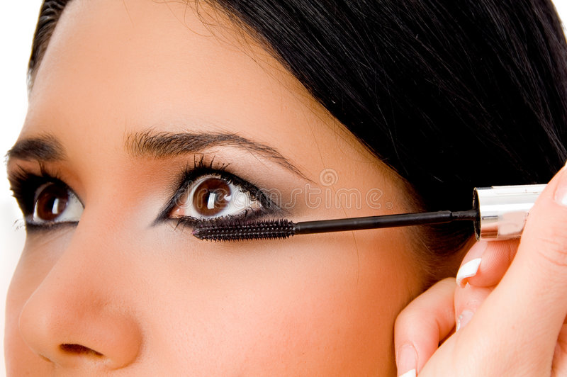 Beautician applying maskara on woman's eye royalty free stock images