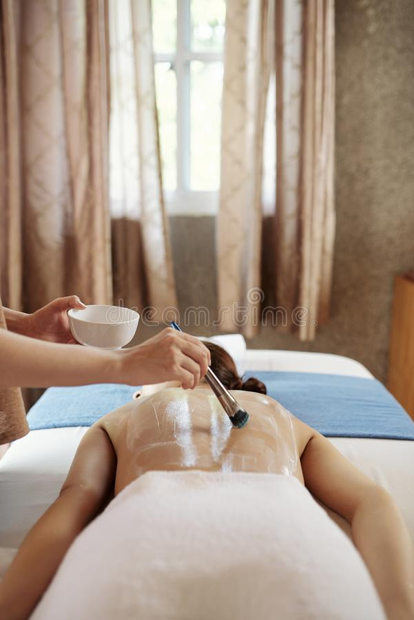Beautician applying nourishing mask. Beautician evenly distributing nourishing mask on back of young female patient royalty free stock images