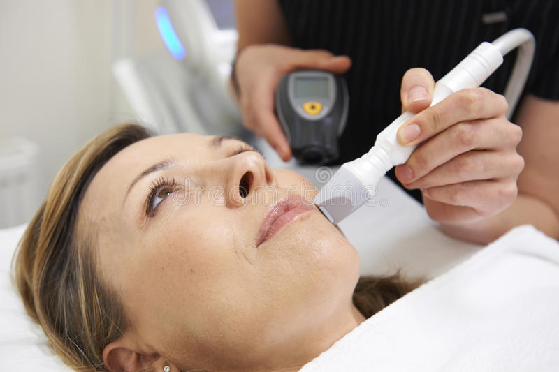 Beautician Carrying Out Ultrasound Skin Rejuvenation Treatment. Female Beautician Carrying Out Ultrasound Skin Rejuvenation Treatment royalty free stock photography