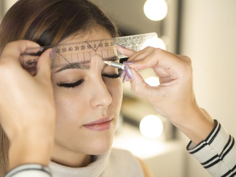 Beautician checks the contour of the eyebrows of young woman client before making permanent makeup with a cosmetic ruler royalty free stock images