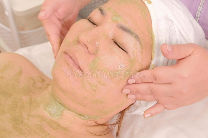Beautician cleans the girl`s face scrub with fruit seeds kiwi. Peeling for face and body. Cosmetic cleansing procedure stock photo