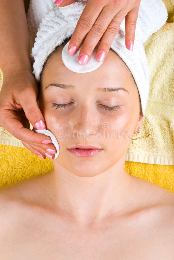 Beautician cleansing young woman face. With pure cotton cosmetic pads and lotion in a spa resort,check also stock images