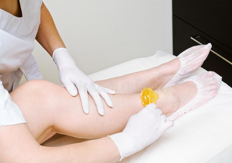 Beautician Cosmetologist που κηρώνει τα θηλυκά πόδια στο σαλόνι κεντρικής ομορφιάς SPA στοκ φωτογραφίες με δικαίωμα ελεύθερης χρήσης