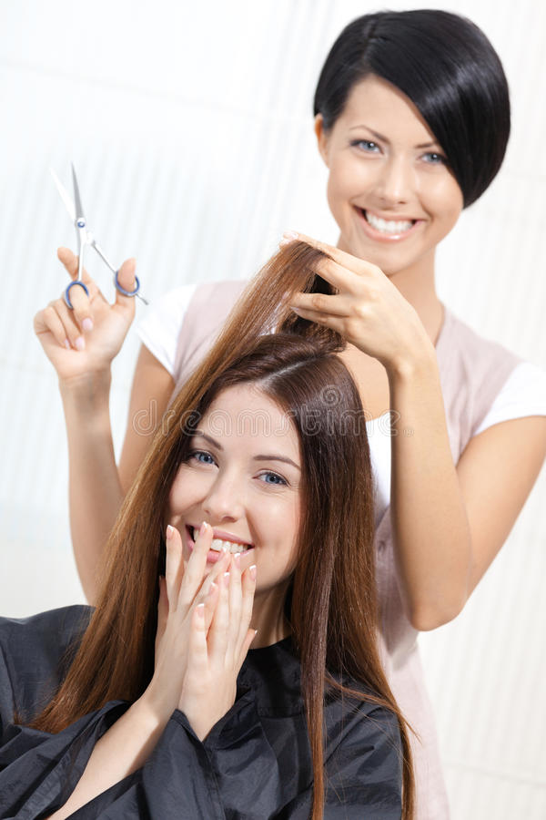 Beautician cuts hair of woman in hairdresser's. Beautician cuts hair of women in hairdresser's. Concept of fashion and beauty royalty free stock photo