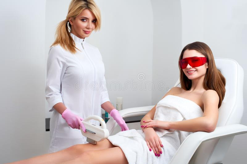 Beautician doctor doing elos hair removal depilation on attractive young woman legs in beuty salon. Hardware aesthetic stock photos