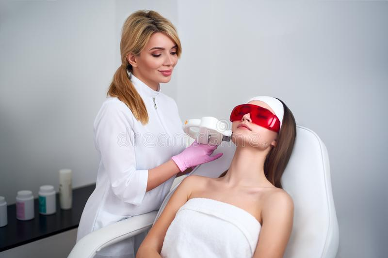 Beautician doctor doing laser RF rejuvenation for pretty young woman face at beauty salon. Elos epilation hair removal royalty free stock photo