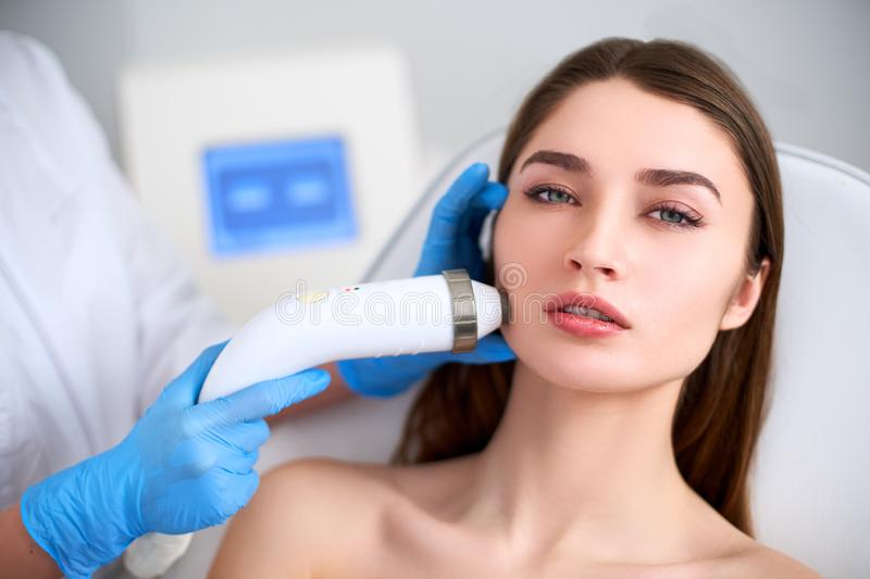 Beautician doctor doing rf-lifting procedure for flawless woman face laying in a beauty salon. Hardware cosmetology stock image