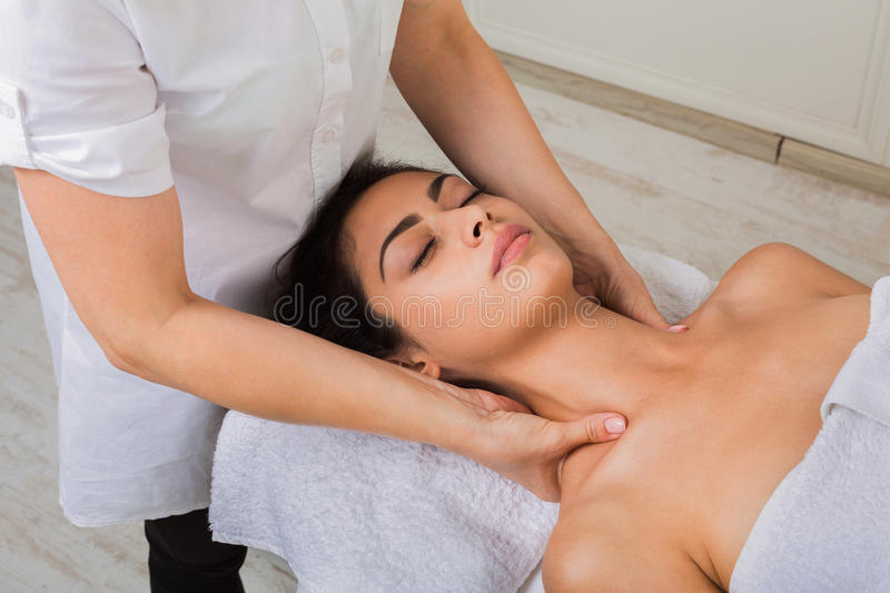 Beautician doctor make neck massage in spa wellness center. Relaxing neck massage in spa to beautiful indian girl. Cosmetology cabinet or beauty parlor stock photography