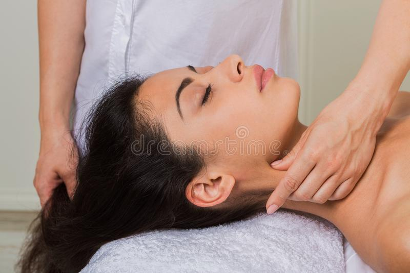 Beautician doctor make neck massage in spa wellness center. Relaxing neck massage in spa to beautiful indian girl. Cosmetology cabinet or beauty parlor royalty free stock photography
