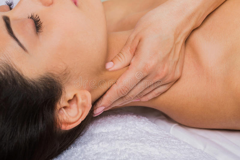 Beautician doctor make neck massage in spa wellness center. Relaxing neck massage in spa to beautiful indian girl. Cosmetology cabinet or beauty parlor royalty free stock photo