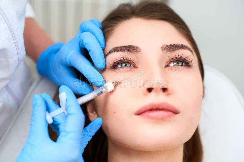 Doctor in medical gloves with syringe injects botulinum under eyes for rejuvenating wrinkle treatment. Filler injection stock photo