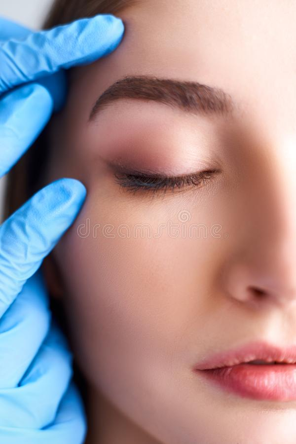 Beautician doctor`s hands in gloves touching face of attractive woman. Fashion blonde model after cosmetic treatment. Aesthetic cosmetology, plastic surgery royalty free stock photography