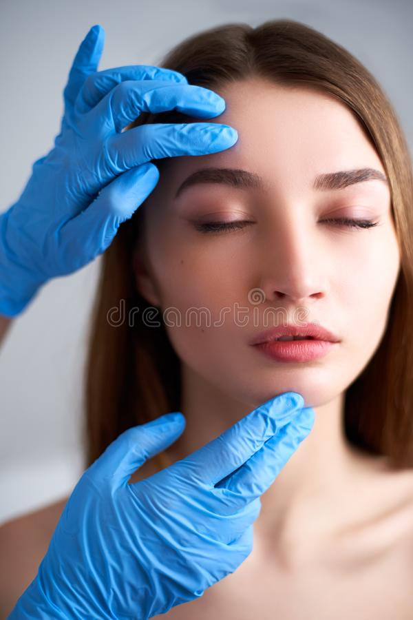 Beautician doctor`s hands in gloves touching face of attractive woman. Fashion blonde model after cosmetic treatment. Aesthetic cosmetology, plastic surgery royalty free stock photo