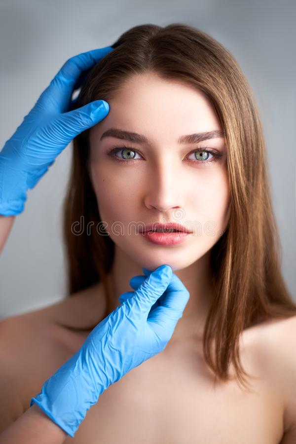 Beautician doctor`s hands in gloves touching face of attractive woman. Fashion blonde model after cosmetic treatment. Aesthetic cosmetology, plastic surgery stock photos