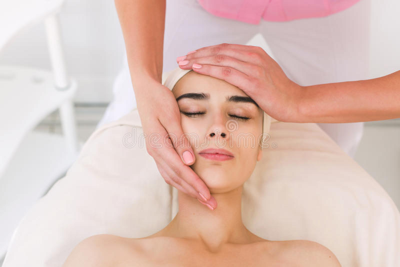 Beautician doing massage of female faces. royalty free stock photos
