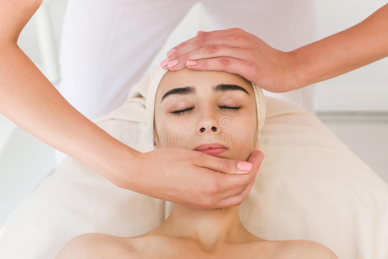 Beautician doing massage of female faces. stock images
