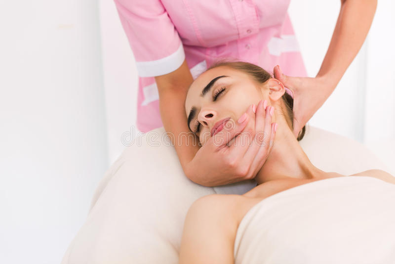 Beautician doing massage of female faces. royalty free stock photo