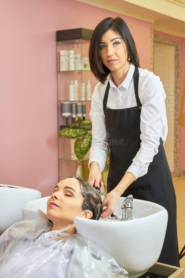 Beautician domycia głowa klient obraz stock