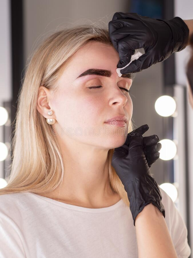 Beautician erases the eyebrow line with a cosmetic cotton pad after shape correction on a eyebrows.  royalty free stock photo