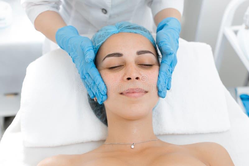 Beautician fait un massage professionnel du visage du patient. Une jeune fille est en train de suivre un cours de soins au spa dan photographie stock libre de droits