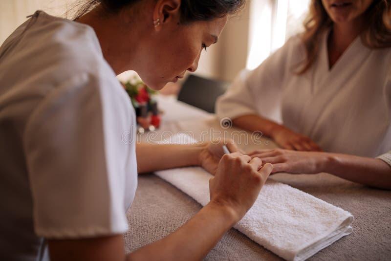 Beautician froterowania i segregowania klientów żeńscy gwoździe obrazy stock