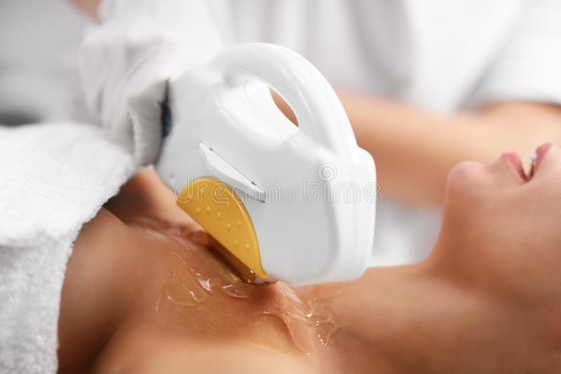Beautician Giving Epilation Laser Treatment To Woman On Cleavage. Picture Of Beautician Giving Epilation Laser Treatment To Woman On Cleavage royalty free stock photo