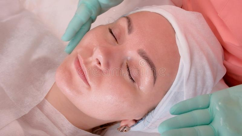 A beautician in gloves puts a moisturizer on the face of a cute girl in a beauty salon. Facial treatment. Cosmetic procedures royalty free stock photo