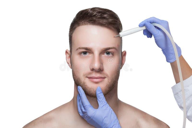 Beautician hace de un hombre un procedimiento para quitar el acné de su cara foto de archivo
