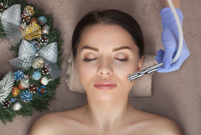 Beautician hace un procedimiento Microdermabrasión a mujer hermosa A su lado hay decoraciones navideñas Año nuevo y fotografía de archivo libre de regalías