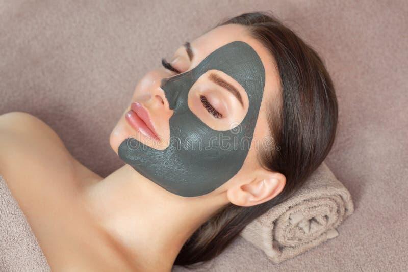 Beautician hace una máscara de arcilla negra para rejuvenecer la piel de una mujer hermosa Concepto de cosmetología y tratamiento imagen de archivo