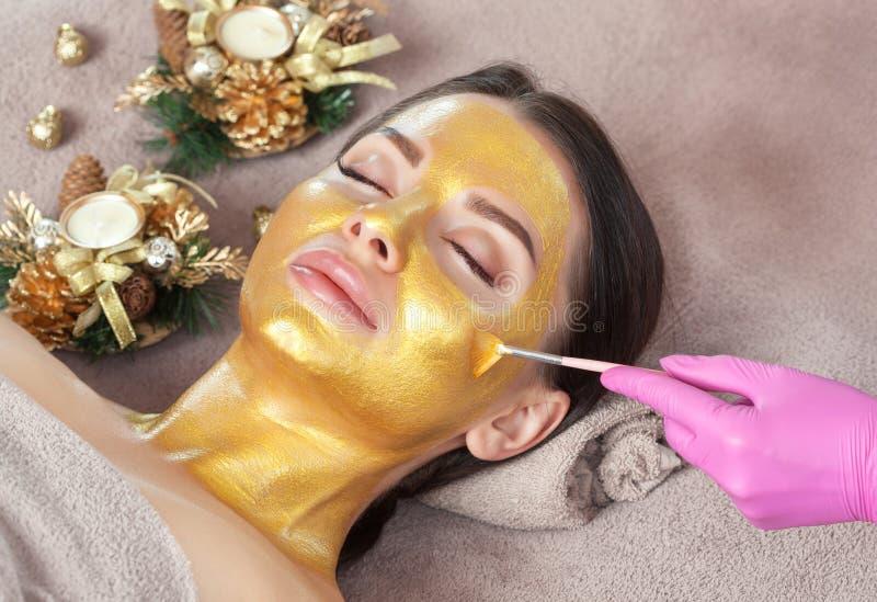 Beautician hace una máscara dorada para rejuvenecer la piel a una mujer hermosa A su lado hay decoraciones navideñas Año nuevo y foto de archivo libre de regalías