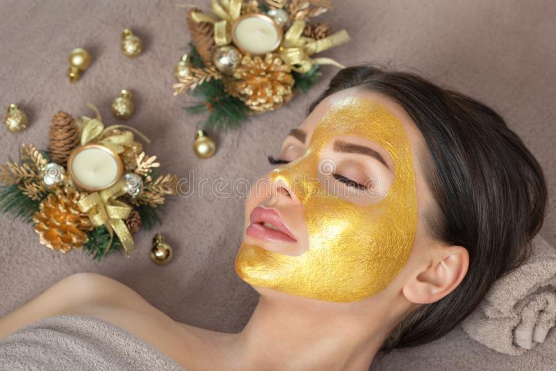 Beautician hace una máscara dorada para rejuvenecer la piel a una mujer hermosa A su lado hay decoraciones navideñas Año nuevo y imagen de archivo libre de regalías