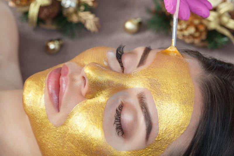 Beautician hace una máscara dorada para rejuvenecer la piel a una mujer hermosa A su lado hay decoraciones navideñas Año nuevo y fotografía de archivo