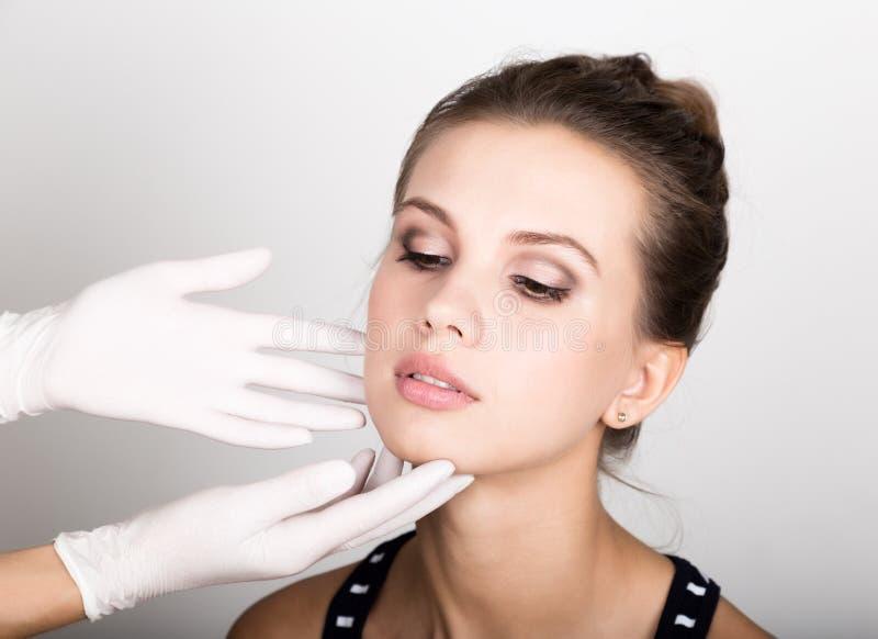 Beautician hand& x27 s που εξετάζει το όμορφο νέο θηλυκό πρόσωπο στοκ εικόνα