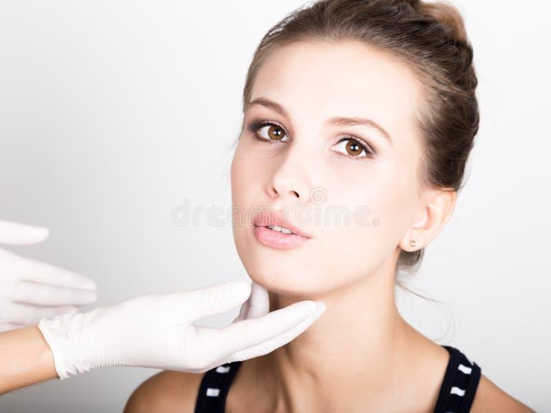 Beautician hand& x27 s που εξετάζει το όμορφο νέο θηλυκό πρόσωπο στοκ εικόνες