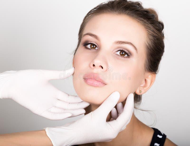 Beautician hand& x27 s που εξετάζει το όμορφο νέο θηλυκό πρόσωπο στοκ εικόνες με δικαίωμα ελεύθερης χρήσης
