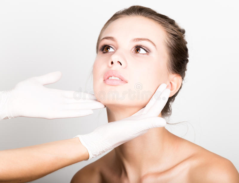 Beautician hand`s examining beautiful young female face. royalty free stock photos