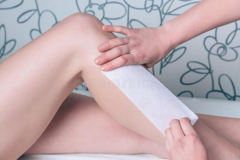 Beautician hands doing depilation in woman legs stock photo
